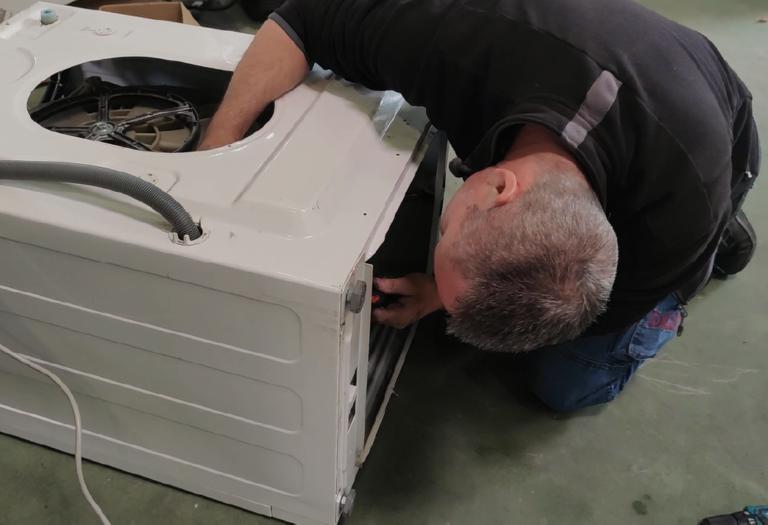 Technicien en plein reconditionnement d'un lave linge